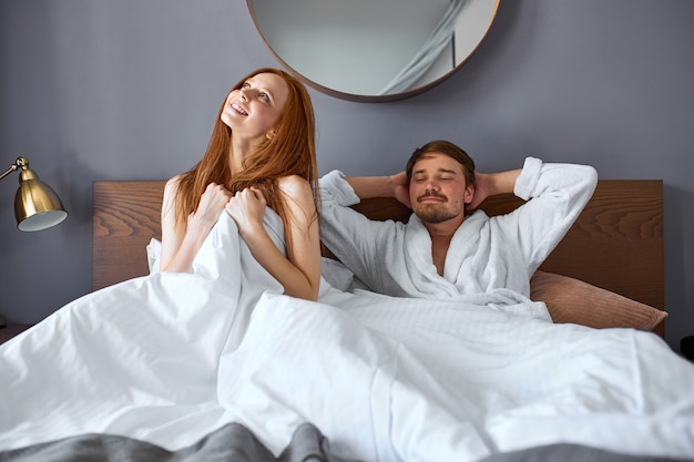 Relaxed couple on bed, have leisure time