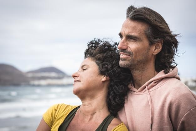 曇りのビーチに面してリラックスしたカップル
