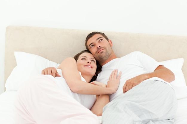 朝の彼らのベッドに一緒に横たわっているリラックスしたカップル