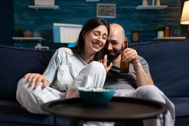 Relaxed couple in pajamas relaxing on sofa eating popcorn watching comedy movie