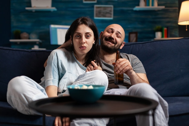 Relaxed couple sitting on couch watching movie on television
