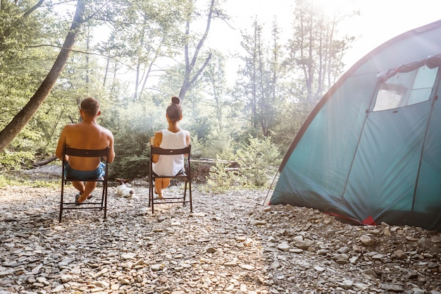 Relaxed couple sitting outside tent while camping nearby mountain river on a sunny day.