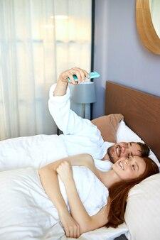 편안한 부부는 침대에서 사진을 찍고, 백인 행복한 남자와 여자는 카메라에 미소