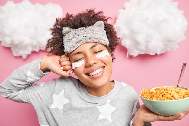 リラックスした巻き毛のアフロアメリカ人女性は、目覚めた後に伸びる幸せな表情を持っています笑顔は広く、上の雲とピンクの壁に隔離されたナイトウェアに身を包んだ健康的な朝食を持っています