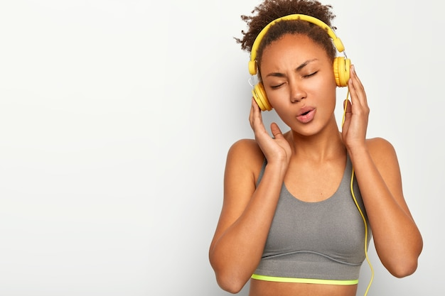편안한 곱슬 머리의 스포티 한 소녀, 실내 운동, 노래 부르기, 헤드폰으로 음악 듣기, 회색 탑 착용