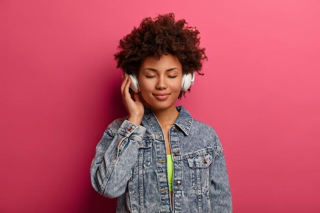 リラックスした巻き毛の女性は、新しいステレオヘッドフォンで音楽を聴きます