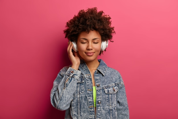 Relaxed curly woman listens music in new stereo headphones