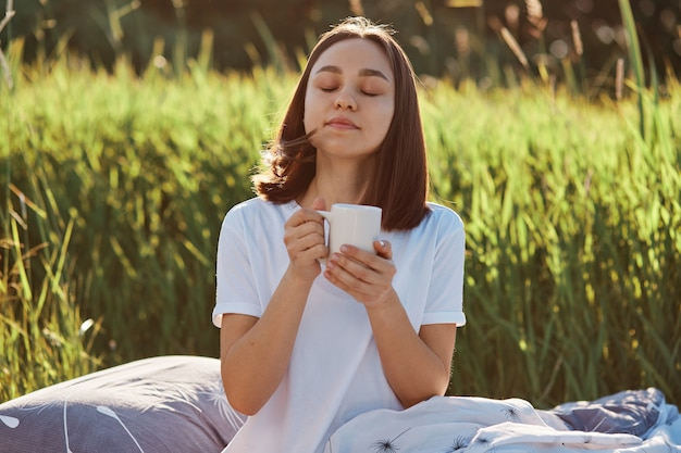 Relaxed dark haired female wearing white casual style t-shirt posing outdoor with cup of hot tea or coffee
