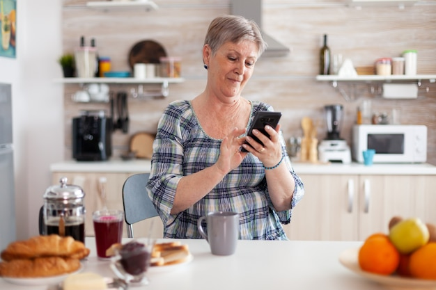 Relaxed elderly woman browsing on phone in kitchen during breakfast. grandma using modern smartphone internet technology, online communication connected to the world, senior leisure time with gadget