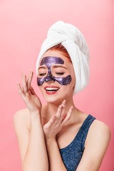 스킨 케어 치료를 하 고 편안한 유럽 소녀. 분홍색 배경에 고립 된 얼굴 마스크와 긍정적 인 여자의 스튜디오 샷.