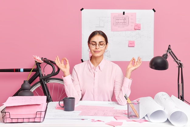 Relaxed european woman worker sits by desk works at home office makes meditation gesture shows mudra sign closes eyes draws sketches and blueprints