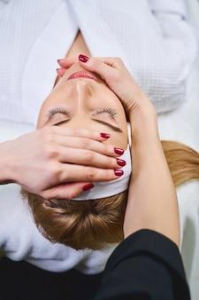 美容師が手の影響で彼女の顔を治療している間、リラックスした女性はソファに横たわっています