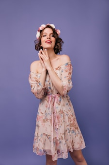 Relaxed female model in spring dress posing. spectacular caucasian lady with roses in hair looking.