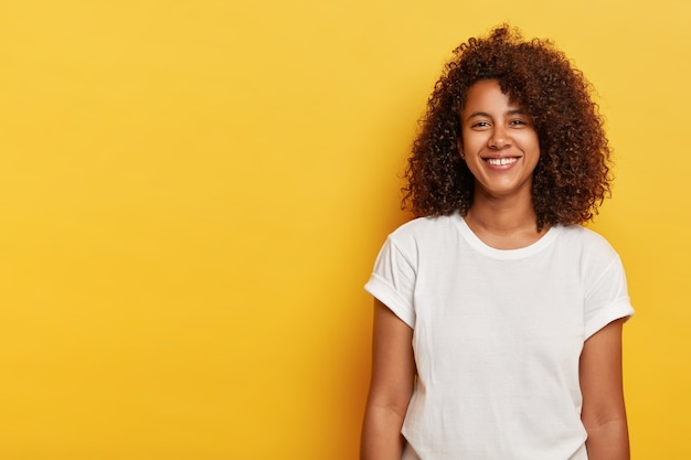 Relaxed female model with curly afro hairstyle, grins from happiness, glad to have successful day, looks straightly , wears white t shirt, laughs indoor over yellow wall, copy space