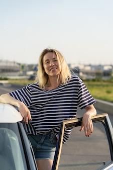 駐車場で車の開いたドアでリラックスした女性のスタンドロードトリップの準備ができて幸せな女性の車の所有者
