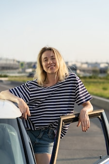 Relaxed female stand at car open door at parking happy woman vehicle owner ready for road trip