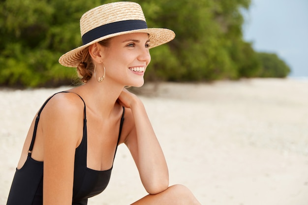 Relaxed female with attractive look has happy expression, tanned skin, wears straw hat and bathing suit, looks on sea or ocean horizon, spends free time on beach. people and recreation concept