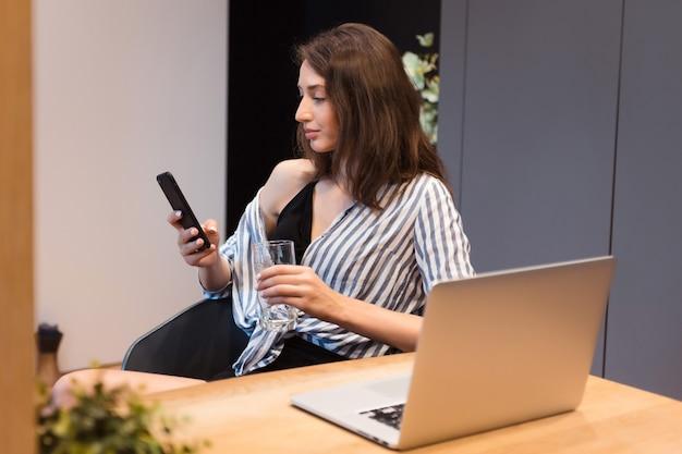 ノートパソコンを開いてオフィスに座り、スマートフォンを使って流行の服を着たリラックスした女性労働者