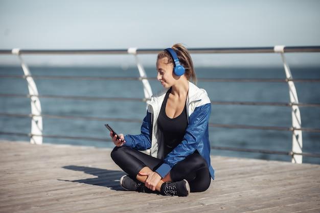 헤드폰이 달린 운동복에 편안한 착용감 여성이 훈련을 위해 스마트 폰에서 음악을 선택합니다.