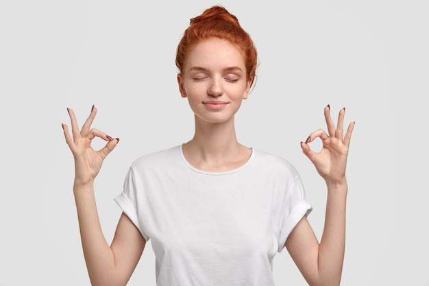 Relaxed foxy girl with freckled soft skin enjoys peaceful atmosphere, keeps hands in mudra sign, relaxed after intense day