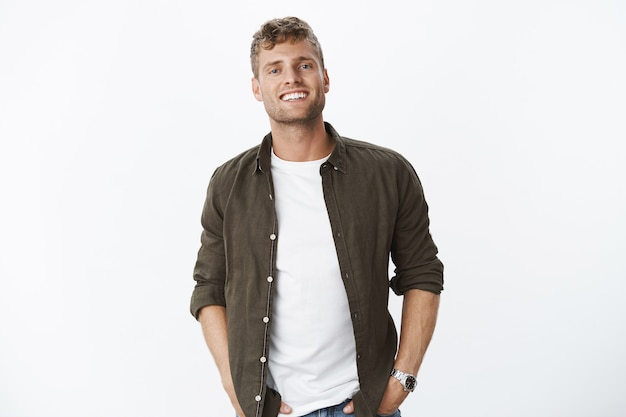 Relaxed, friendly good-looking european guy with bristle smiling joyfully with white healthy teeth holding hands in pockets being happy and satisfied, posing cheerfully over white wall