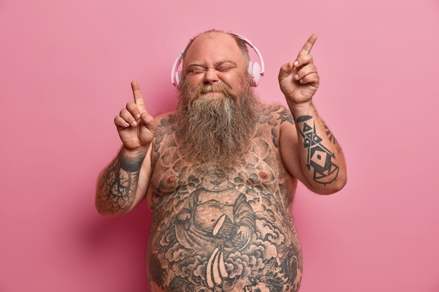 Relaxed funny thick man with naked body, tattooed arms and stomach, dances while listens music, moves arms and closes eyes in enjoyment, wears headphones on ears, has fun and feels aspiration