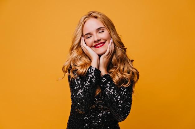 Расслабленная девушка в черном платье позирует с улыбкой. беззаботная блондинка, изолированные на желтой стене.