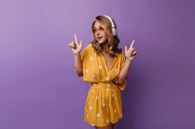 Расслабленная девушка в оранжевой одежде слушает музыку и танцует. кавказская молодая женщина jocund позирует на фиолетовом в наушниках.