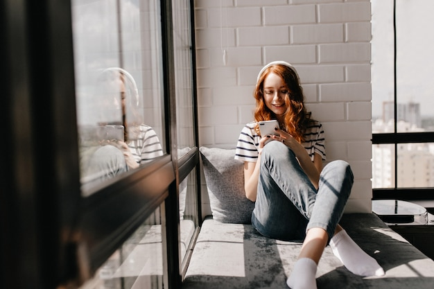 Relaxed girl in jeans sitting on window sill. magnificent ginger lady in headphones holding phone.