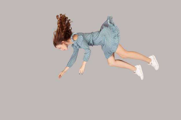Расслабленное платье девушки с рюшами и вьющимися парящими волосами, левитирующими, летящими во сне с поднятыми руками