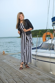 Relaxed girl in striped overall on pier