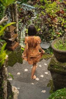그녀의 드레스를 만지고 기대하는 편안한 소녀, 테라스로 단계적으로 이동