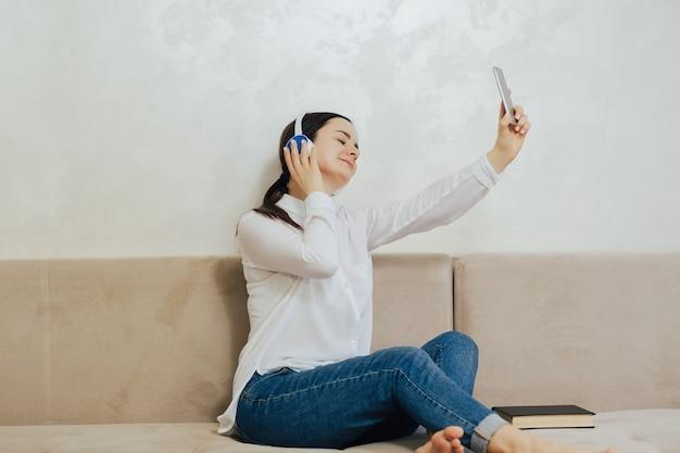 헤드폰에 닫힌 눈을 가진 편안한 소녀는 현대 스마트 폰에서 음악을 들으면서 거실의 아늑한 소파에 휴식을 취합니다.