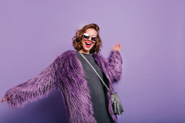 Расслабленная девушка с серым кошельком, стоящая в уверенной позе на фиолетовом фоне