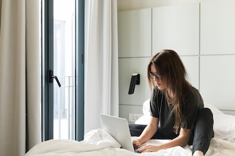 Relaxed girl with laptop on bed