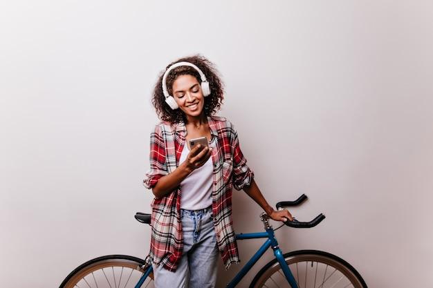 Ragazza rilassata con il telefono in piedi vicino alla bicicletta e sorridente. affascinante donna africana ascoltando musica e messaggi di testo.