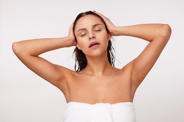 Rilassata bella giovane femmina bruna mantenendo gli occhi chiusi mentre posa con i capelli bagnati e vestita in asciugamano da bagno, tenendo la testa con le mani alzate