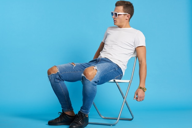 Relaxed guy in jeans with torn knees sits on a chair indoors on a blue background with full-length