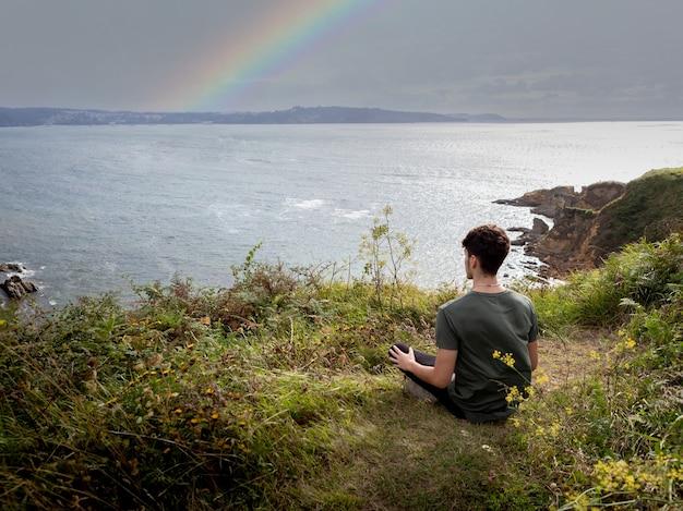 Расслабленный парень сидит на траве медитирует