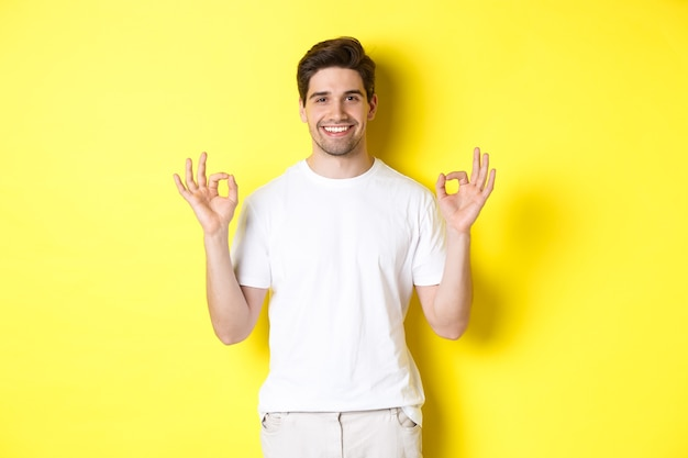Relaxed guy smiling, showing okay signs, approve or agree, standing against yellow background.