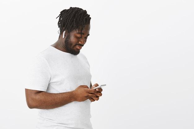Расслабленный парень с косами позирует на белой стене со своим телефоном