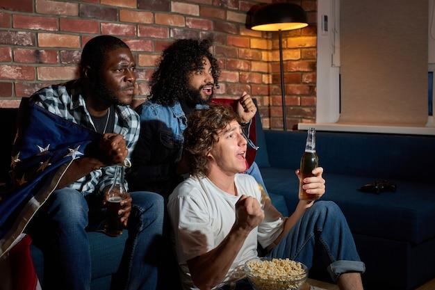 집에서 축구 스포츠 경기를보고 편안한 남자. 친구의 다민족 그룹, 좋아하는 국가 대표팀을 응원하는 팬, 맥주를 마시고 있습니다. 감정, 지원, 스포츠 경쟁의 개념