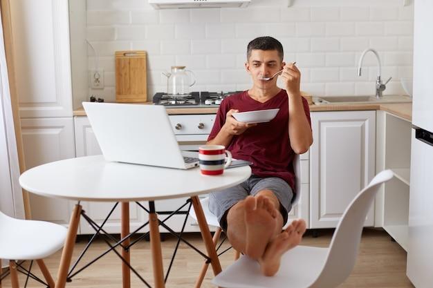 Bell'uomo rilassato che indossa una maglietta casual marrone seduto al tavolo, mette i piedi sulla sedia, mangia la zuppa e guarda un film, si gode la colazione durante il fine settimana o durante una pausa dal lavoro online.