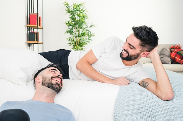 Relaxed handsome young gay couple looking at each other