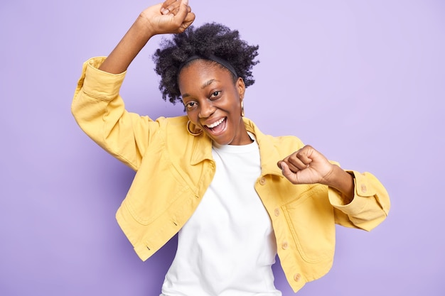 Relaxed happy afro america woman dances and has fun raises hands uo carefree enjoys music