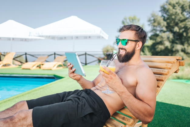 Relaxed and happy guy sits on sunbed and smiles. he holds tablet and looks on it. man wears sunglasses. he holds cocktail in left hand. he is sitting besides swimming pool. guy is satisfied.