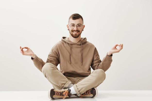 Расслабленный счастливый хипстерский парень сидит на полу и медитирует, сохраняйте спокойствие