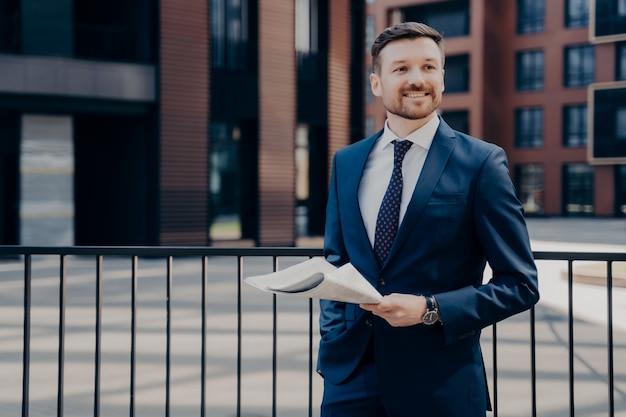 屋外の休憩時間に新聞を持って立って、新鮮なニュースを読んで、笑顔で周りを見回し、彼の後ろにオフィスビルと立っている間幸せを感じて青いスーツを着てリラックスした幸せな男性サラリーマン