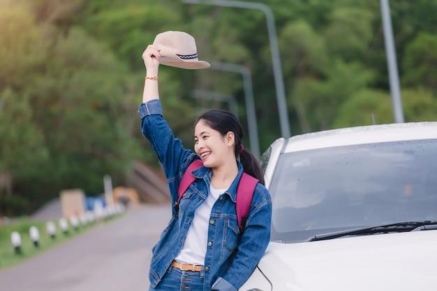 車の窓から自然の景色を見て夏のロードトリップ旅行休暇でリラックスした幸せな女