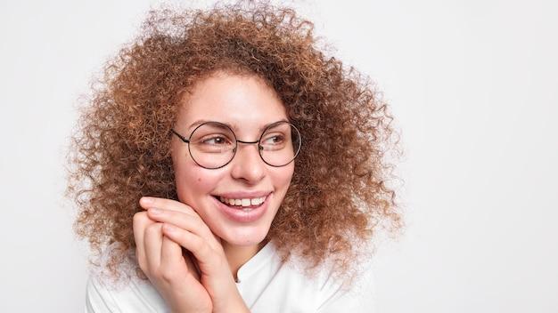 곱슬 덥수룩 한 머리카락을 가진 편안한 행복한 여자는 얼굴 미소 근처에 손을 유지하며 홍보를 위해 흰 벽 빈 복사본 공간에 대한 시력 교정 모델을위한 둥근 안경을 착용하고 좋은 하루를 즐깁니다.
